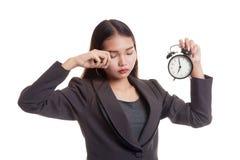 Сонная молодая азиатская бизнес-леди с часами в утре Стоковые Изображения RF