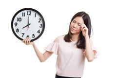 Сонная молодая азиатская бизнес-леди с часами в утре Стоковая Фотография RF