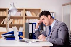 Сонный бизнесмен работая в офисе Стоковое фото RF