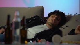 Сонный пьяный человек имея головную боль после партии дома, пустые бутылки на таблице сток-видео