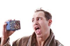 Сонный рассерженный человек с будильником в руке в самом начале mor Стоковые Фото