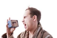 Сонный сердитый человек крича в будильнике в раннем утре Стоковые Фото