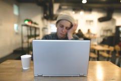 Сонный фрилансер сидит в уютном кафе и работает для компьтер-книжки Битники в кафе с компьтер-книжкой Фокус на компьтер-книжке Стоковые Фото
