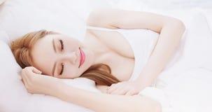 Сон женщины на кровати стоковая фотография
