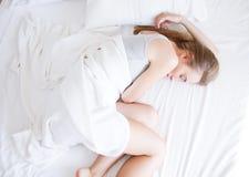 сон Молодая женщина спать в кровати, женский отдыхать на удобной кровати с подушками в белых постельных принадлежностях в светлой стоковое фото