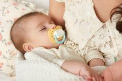 Сон младенца в руке матери, счастливой концепции материнства Стоковая Фотография