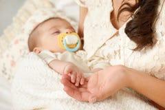 Сон младенца в руке матери, счастливой концепции материнства Стоковое Изображение RF