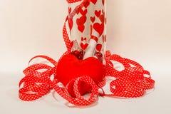 Сообщение в бутылке с Хартами на ей и красная лента вокруг ее и красного Харта Стоковые Изображения