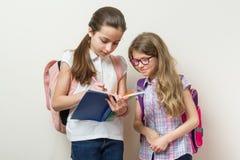 Сообщение 2 девушек на школе Школьницы с рюкзаками, книгами, стеной предпосылки яркой на школе стоковое изображение rf