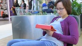 Сообщение девушки печатая на пусковой площадке в торговом центре видеоматериал