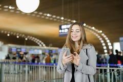 Сообщение женщины печатая smartphone на авиапорте, нося пальто Стоковая Фотография