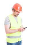 Сообщение занятого мужского подрядчика печатая на smartphone Стоковое Изображение
