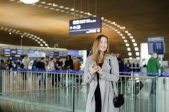 Сообщение красивой молодой женщины печатая smartphone на авиапорте, нося пальто Стоковое Изображение