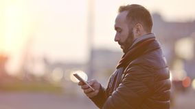 Сообщение куртки и шарфа молодого задумчивого мужчины портрета нося печатая используя смартфон акции видеоматериалы