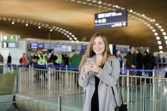 Сообщение милой женщины печатая smartphone на авиапорте, нося пальто Стоковые Изображения RF