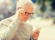 Сообщение отправке SMS старшего человека на смартфоне в городе стоковые фотографии rf