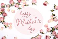 Сообщение приветствию дня матерей с малыми розовыми розами на задней части белизны Стоковые Фотографии RF