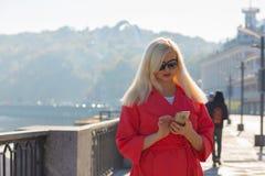 Сообщение привлекательной зрелой женщины печатая на мобильном телефоне, представляя в лучах солнца Космос для текста стоковые изображения