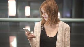 Сообщение сочинительства женщины детенышей довольно рыжеволосое используя ее smatphone Городская предпосылка ночи видеоматериал