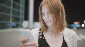 Сообщение сочинительства женщины детенышей довольно рыжеволосое используя ее smatphone Городская предпосылка ночи сток-видео