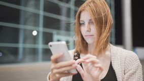 Сообщение сочинительства женщины детенышей довольно рыжеволосое используя ее smatphone Городская предпосылка ночи акции видеоматериалы