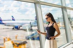 Сообщение сочинительства молодой женщины на телефоне пока ждущ стоковая фотография rf