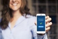 Сообщение сделки завершенное Женщина показывая ее мобильный телефон стоковое фото