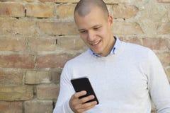 Сообщение чтения молодого человека с умным телефоном стоковое фото rf