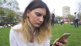 Сообщение чтения молодой женщины на телефоне в парке акции видеоматериалы
