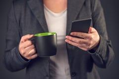 Сообщение sms чтения коммерсантки на перерыве на чашку кофе Стоковые Фото