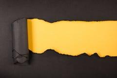 Сорванная бумага, космос для экземпляра желтый цвет предпосылки черный Стоковые Фото