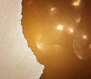 Сорванный бумажный край над мягкими и мечтательными золотыми светами bokeh стоковое изображение rf