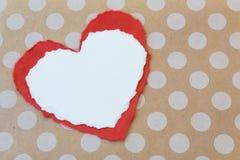 2 сорванных бумажных сердца отдыхая на предпосылке бумаги kraft точки польки Стоковая Фотография RF