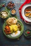 Сортированная индийская еда Шары с сыром paneer, карри, рисом, naan хлебом, samosas, цыпленком, чатнями и специями на темном дере Стоковая Фотография