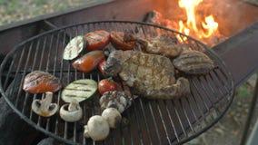 Сортированное мясо с sprigs розмаринового масла и зажаренным концом-вверх овощей, главный кашевар с схватами извлекает сваренную  сток-видео