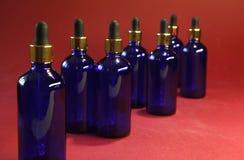Сортированные бутылки синего стекла с золотой капельницей на красной предпосылке Стоковая Фотография