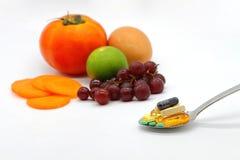 Сортированные витамины и питательные дополнения в ложке сервировки на предпосылке плодоовощей нерезкости красочной стоковые изображения rf