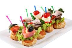 Сортированные канапе-сандвичи на плите над белой предпосылкой Стоковая Фотография RF
