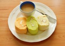 Сортированные крен варенья и кофейная чашка с вилкой на плите Стоковое Изображение