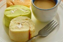 Сортированные крен варенья и кофейная чашка с вилкой на плите Стоковые Изображения