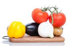 Сортированные овощи на разделочной доске на белой предпосылке Стоковое Изображение RF