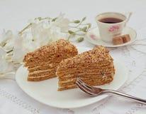 Сортированные причудливые изысканные пирожные на плите Пирожные меда с красивым украшением над белой винтажной предпосылкой шнурк Стоковая Фотография RF
