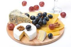 Сортированные сыры, виноградины и бокал вина на деревянной доске Стоковые Фото