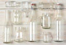 Сортированные ясные стеклянные бутылки на белой древесине Стоковая Фотография RF