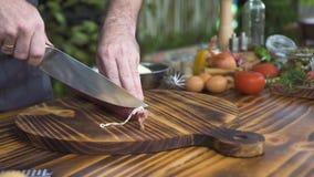 Сосиска вырезывания повара шеф-повара на конце деревянной доски вверх Мужские руки сосиски вырезывания повара для варить пиццу пр сток-видео