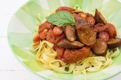 Сосиска Chorizo и еда макаронных изделий томата с базиликом в isolat плиты Стоковое Изображение