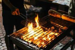 Сосиски жарят с горящим углем с огнем на плите с грилем на верхней части в Бангкоке, Таиланде Стоковое Фото
