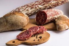 Сосиски и темный хлеб изолированные на белой предпосылке стоковые фото