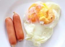 Сосиски и яичница положенные в тарелку иллюстрация вектора