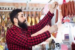 Сосиски молодого мужского клиента рассматривая в butcher's ходят по магазинам Стоковые Фотографии RF
